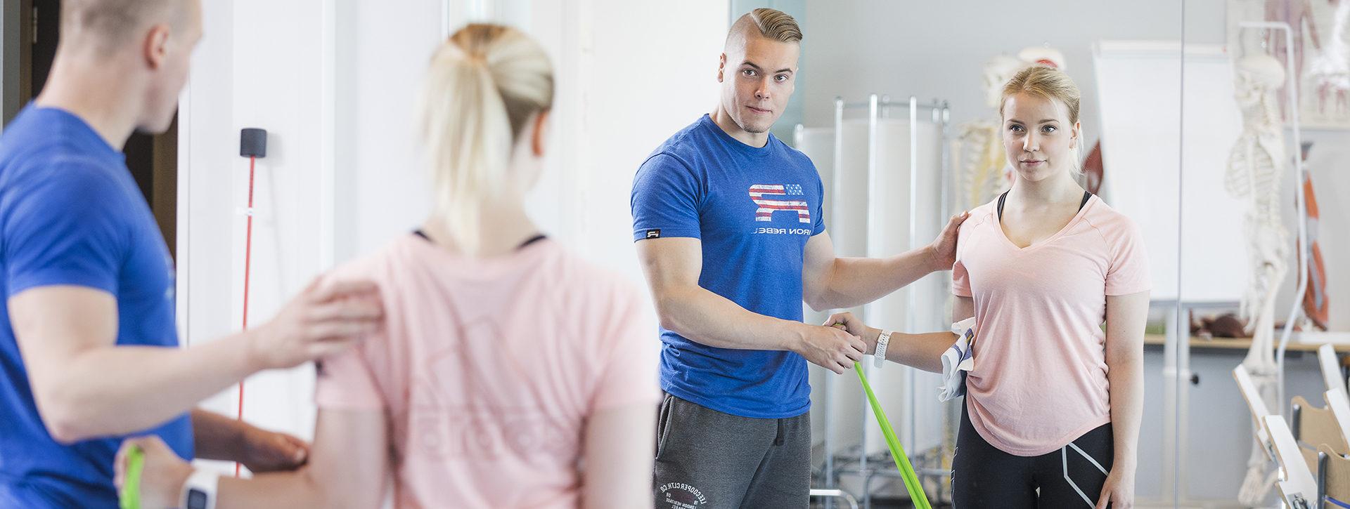Fysioterapian opiskelijat harjoittelevat peilin edessä asiakkaan ohjausta.