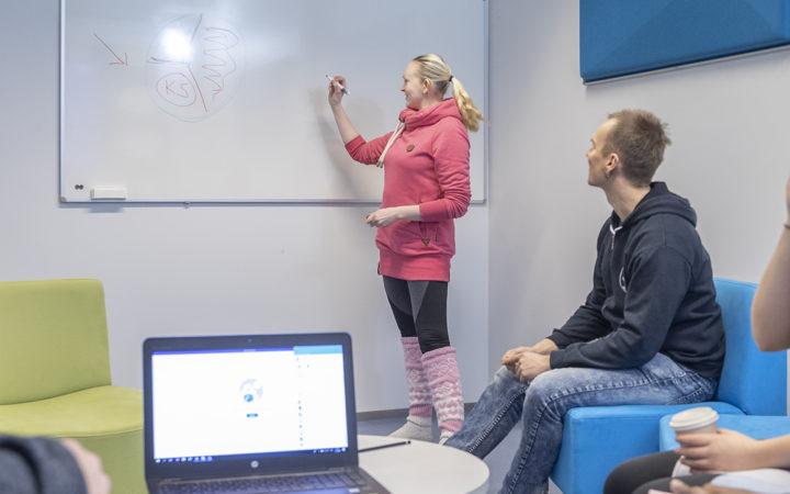 Yhteisöpedagogi opiskelijat tekevät ryhmätyötä valkotaulun ja tietokoneen äärellä