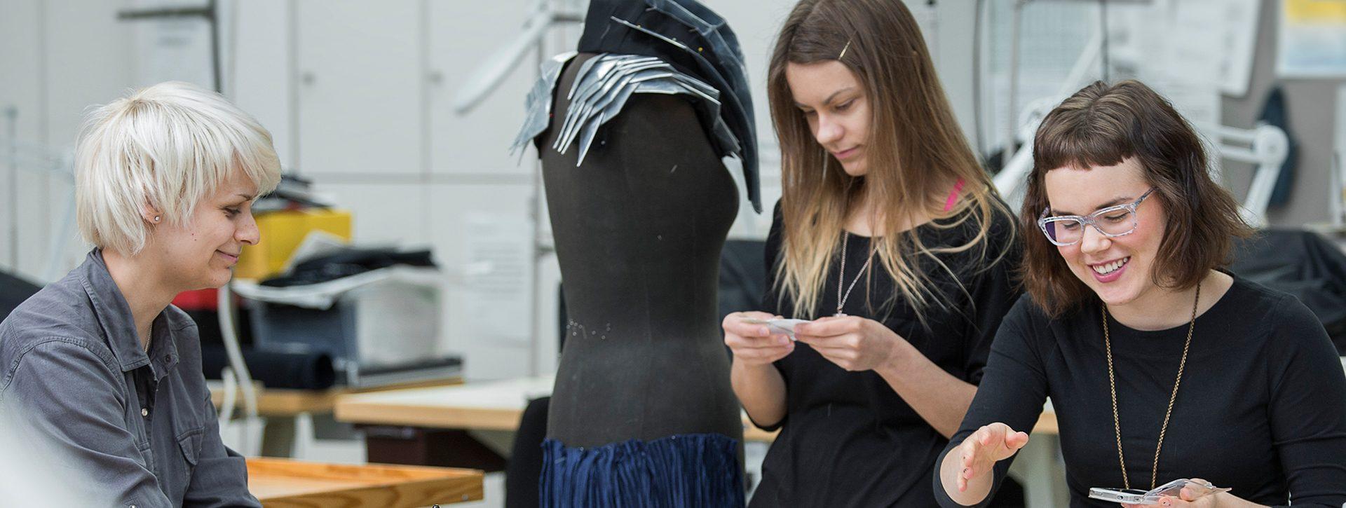 Muoti ja puvustus -opiskelijat sommittelevat vaatetta mallinuken päälle.