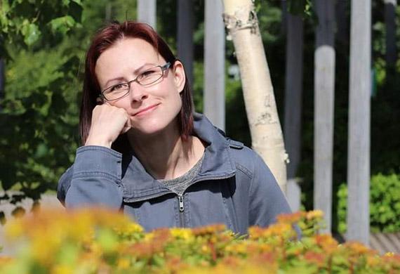 Nainen istuu vihreän pensaan takana.