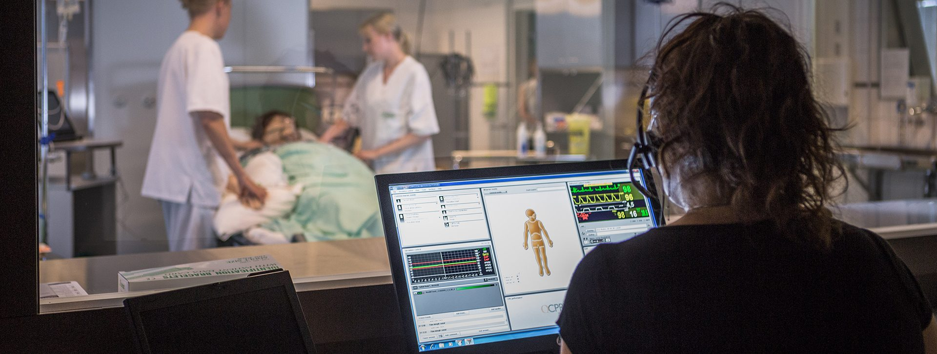 Taustalla kaksi sairaanhoitaja opiskelijaa harjoittelevat hoitotilannetta simuaatiotilassa. Etualalla opettaja valvoo tilannetta ikkunan läpi ja tarkkailee harjoitusnukesta saatavia tietoja tietokoneelta.