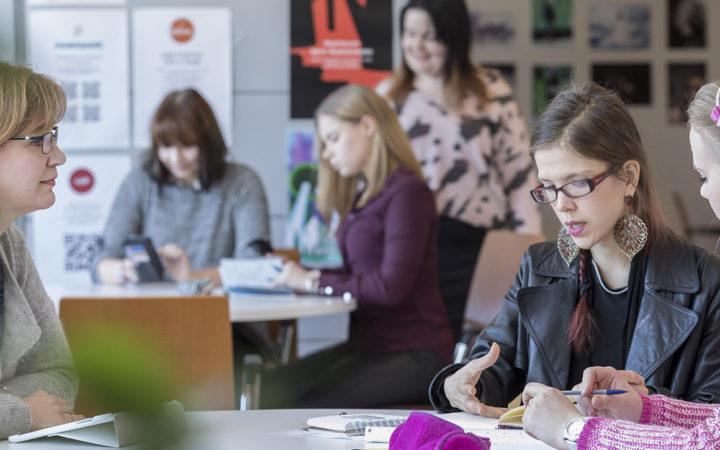 Opiskelijat tekevät ryhmätyötä pöytien ääressä