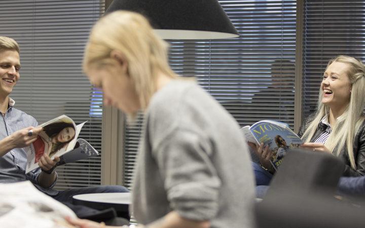 Opiskelijat lukevat sanomalehtiä ja juttelevat kirajston lukusalissa