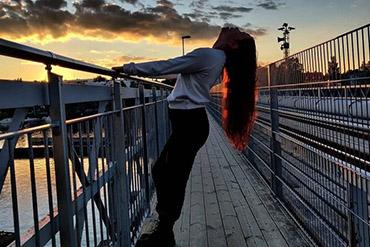 Tyttö seisoo sillalla.