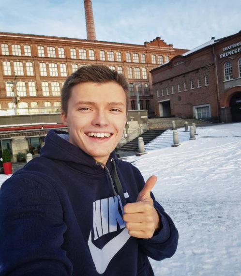 Tubettaja Kirill Sultanshin peukuttaa Tampereella, taustalla tiilinen tehdasrakennus