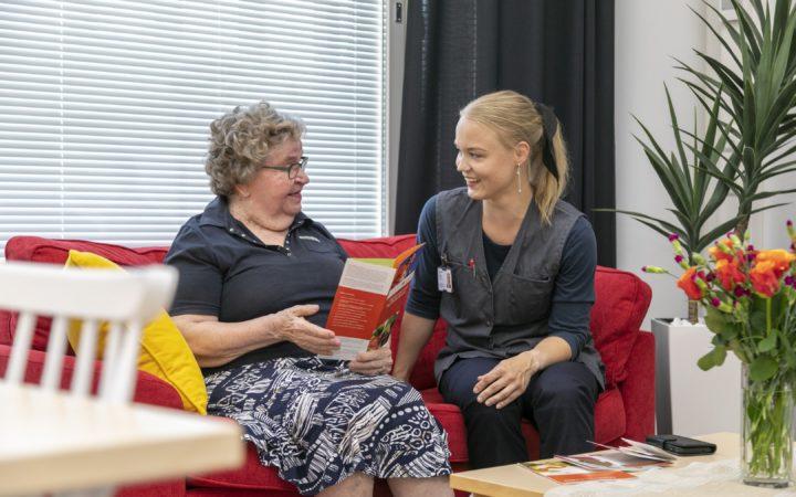 Iäkäs nainen tutkii esitettä yhdessä kotihoidon hoitajan kanssa.