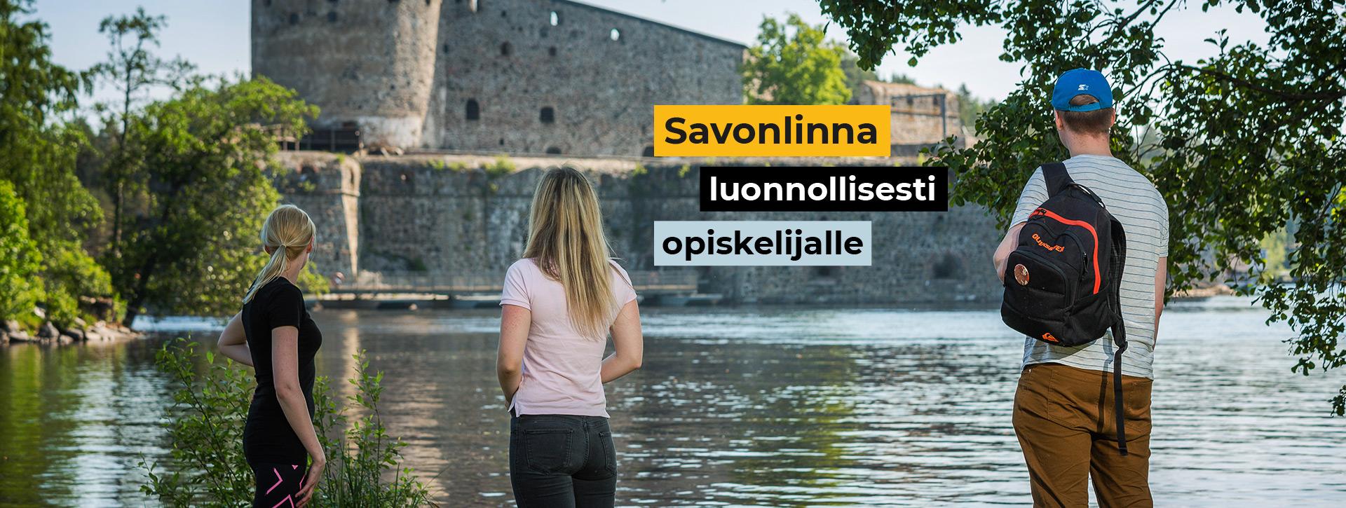 Kaksi nuorta naista ja yksi nuori mies katsovat Olavinlinnaa kohti