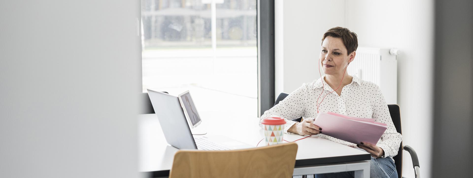 Keski-ikäinen nainen istuu pöydän äärellä, tietokoneen edessä. Hänellä on nappikuulokkeet korvissa.