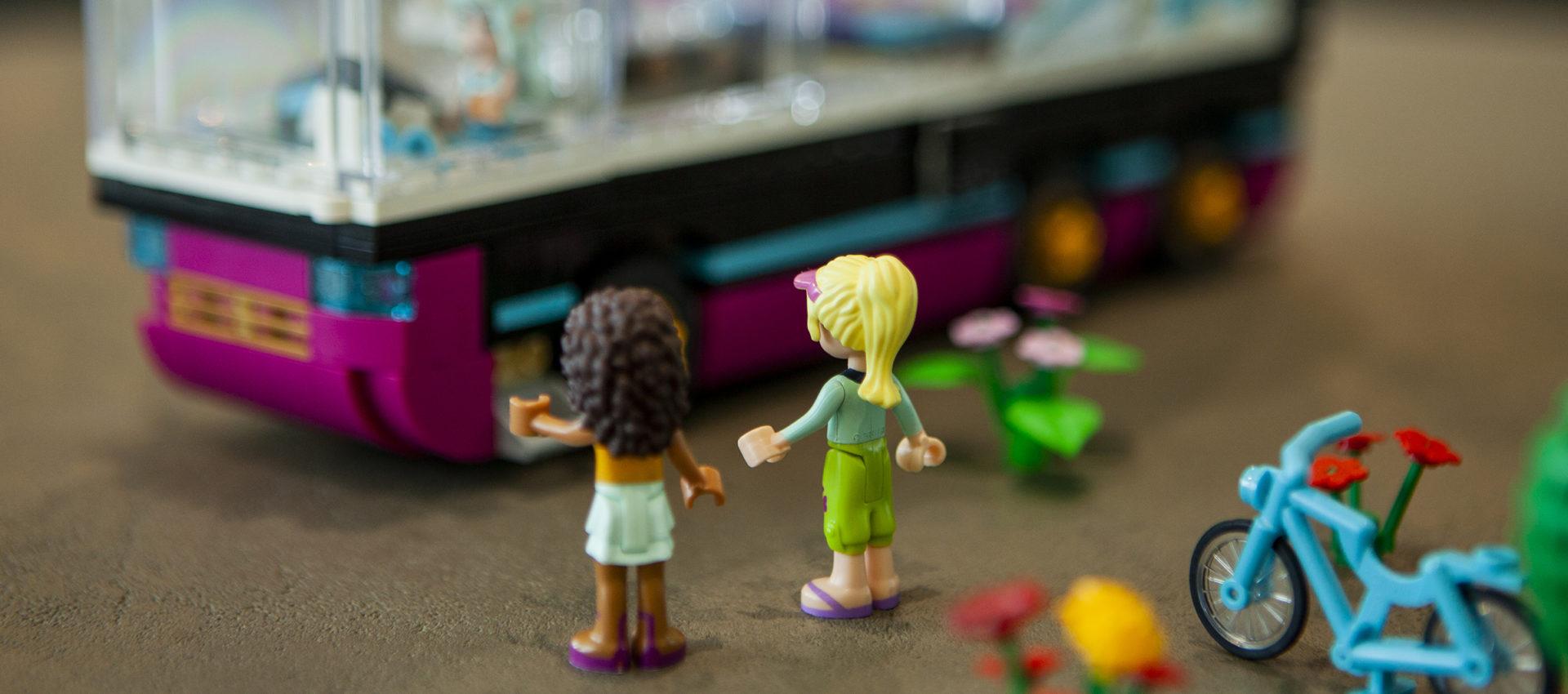 Legohahmoista tehty kuva, jossa kaksi koululaista odottaa bussia.