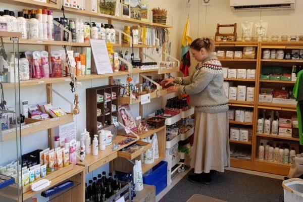 Kuvassa PuotiMaalla-puodin yrittäjä Liisa Mattila järjestää myymälän hyllyjä, jotka ovat täynnä erilaisia tuotteita. Kuvan on ottanut Tommi Mattila.