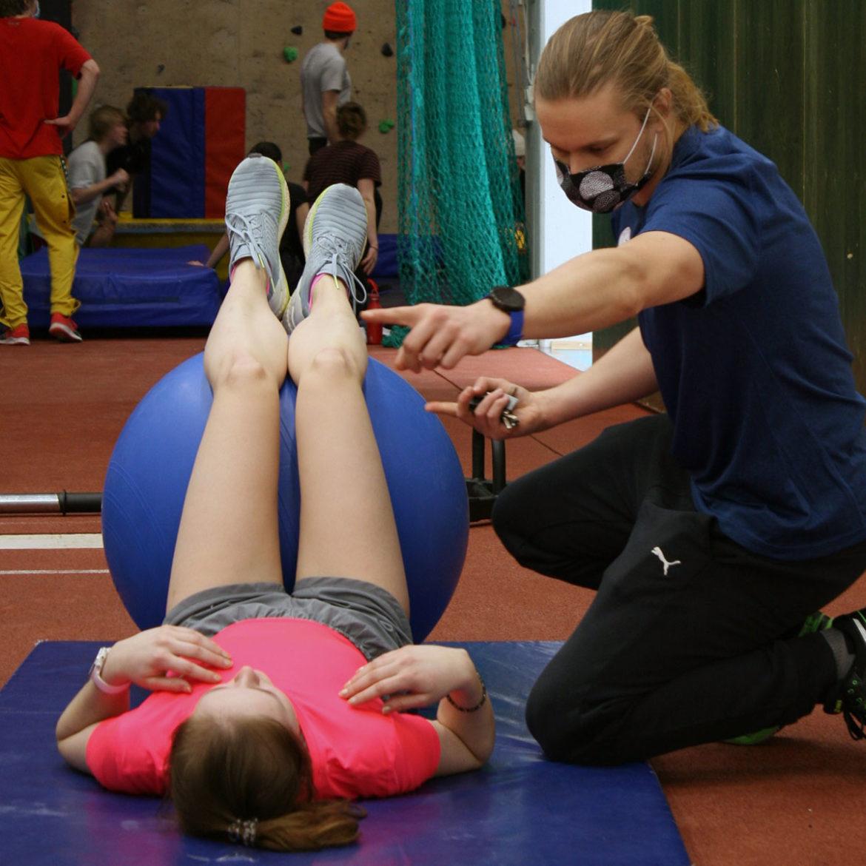 Naprapaatti Niko Leinonen ohjaa jumppamatolla makaavaa opiskelijaa.