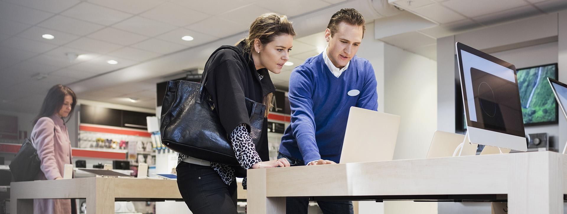 Nainen ja mies katsovat yhdessä tietokonetta aulatiloissa.
