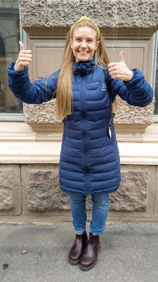Kuva nuoresta naisesta seisomassa ulkona ja peukuttamalla iloisesti.