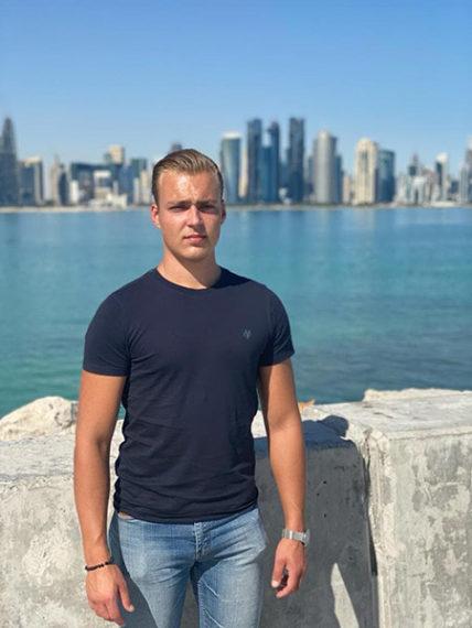 Nuori mies seisomassa meren rannalla.