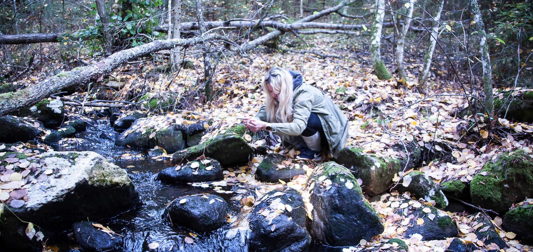 Syksyisessä metsässä virtaa joki. Nainen kurottaa nostamaan vettä käsillään.