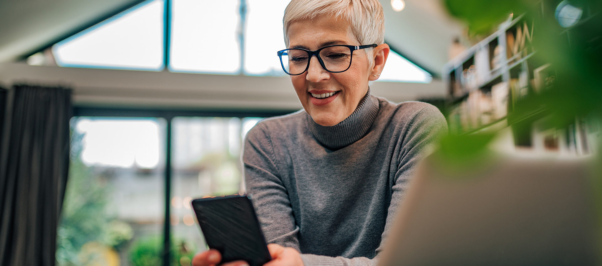 Close-up portrait of a happy senior woman looking at smart phone while sitting at desk with laptop.