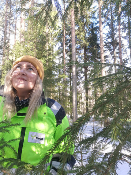 Nuori nainen seisoo metsässä ja katselee puita.