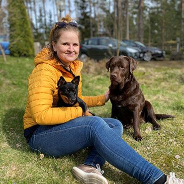 Nuori nainen istuu nurmikolla kahden koiran kanssa.