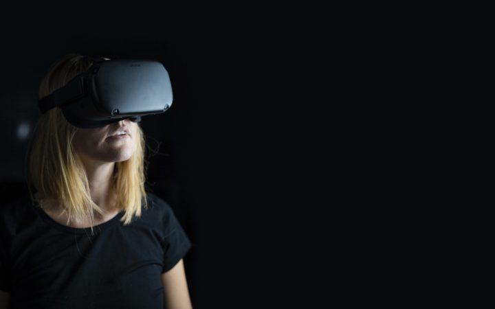 Naisella on päässä virtuaalilasit. Katse on suunnattu oikealle.