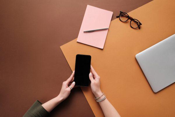 Kuva otettu ylhäältäpäin. Henkilö pitelee älypuhelinta käsissään, jotka lepäävät pöydän päällä. Pöydällä myös tyhjiä papereita, kynä ja silmälasit.