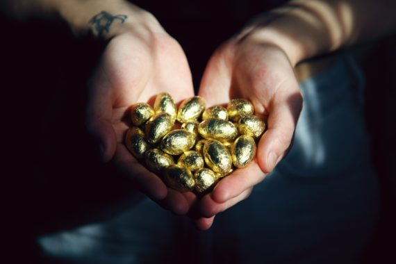 Person holding golden chocolate eggs in hands