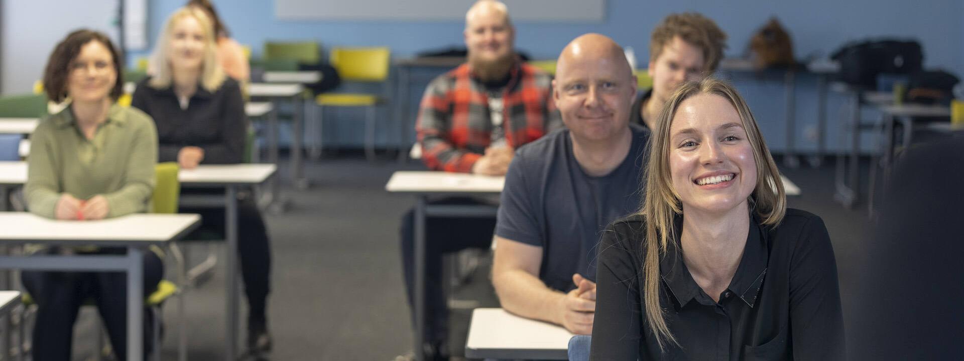Hymyileviä opiskelijoita luokassa istumassa.