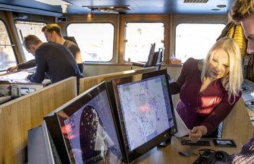 Kuvassa nuoria ihmisiä laivan komentosillalla.