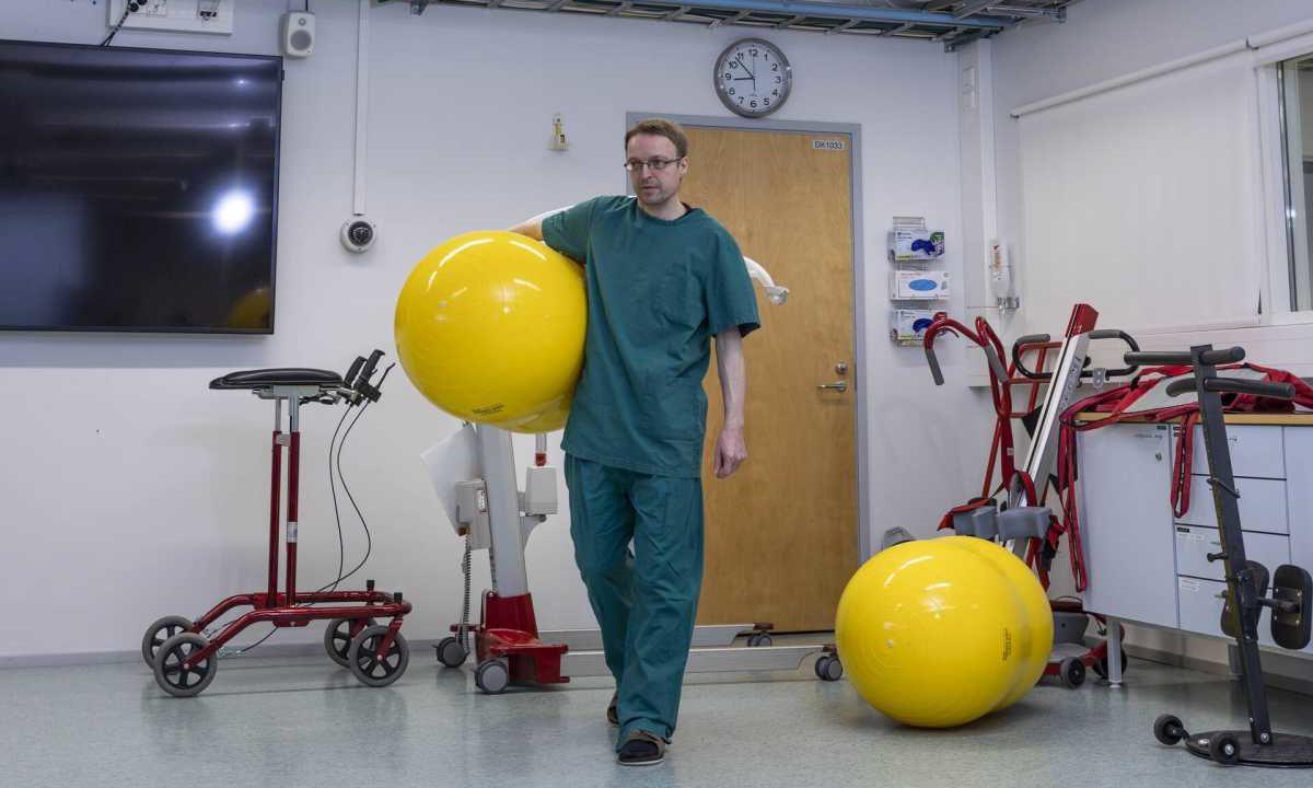 Sairaanhoitaja mies kävelee jumppapallo kainalossa.