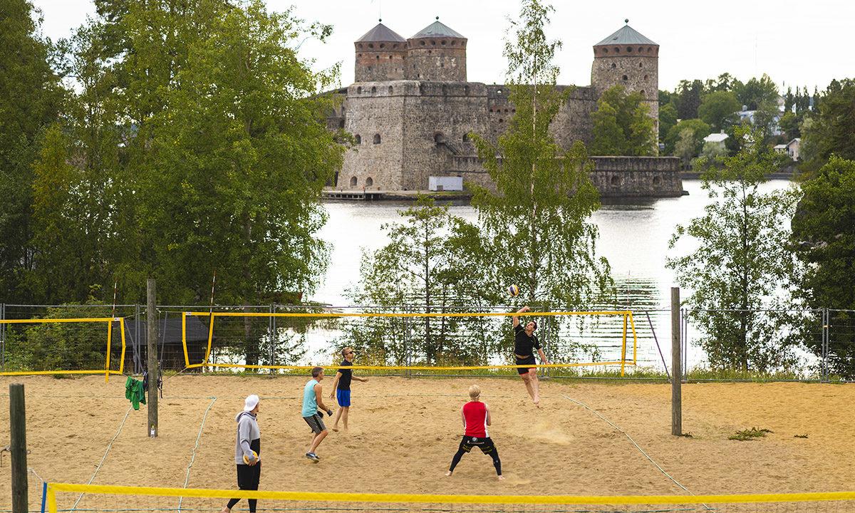 Ihmisiä pelaamassa ulkona lentopalloa, taustalla järvi ja Olavinlinna.