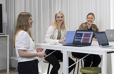 Kolme naista tietokoneiden äärellä.