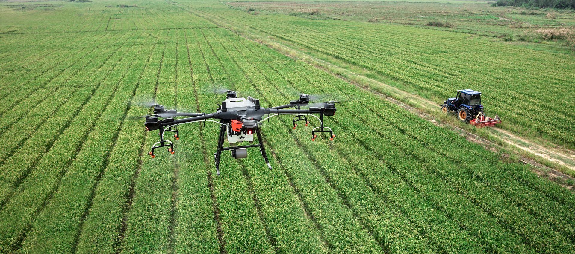 Kuvassa näkyy iso pelto, jonka päällä lentää drone. Alhaalla näkyy traktori.