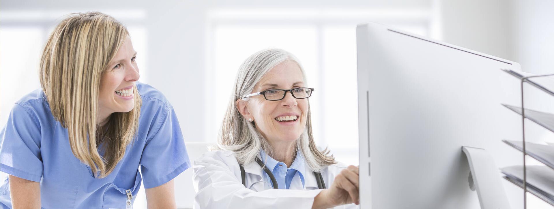Kaksi hoitoalan naistyöntekijää koneen äärellä työskentelemässä.