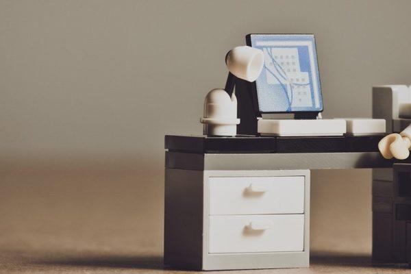 Työpöydän ääressä hahmo, jolla on melkoisen toivoton ilme kasvoillaan