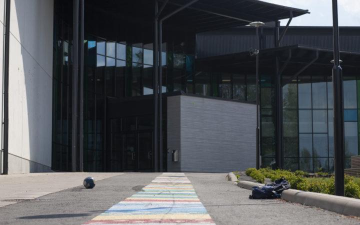 Koulun pääsisäänkäynti, jota ympäröivät korkeat lasiseinät. Etualalla käsin maalattu värikäs raidallinen polku kohti ovea. Maassa jalkapallo ja reppu. Säätila aurinkoinen ja kesäinen.