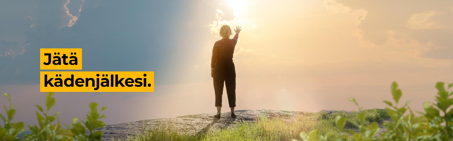 Nainen seisoo kalliolla ja kohottaa käden kohti aurinkoa.