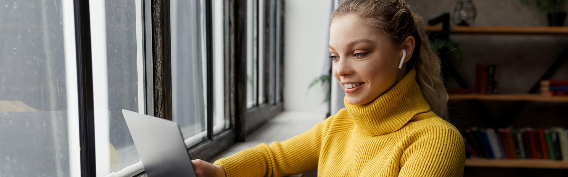 Nuori nainen katsoo hymyillen tietokonetta ikkunan edessä.