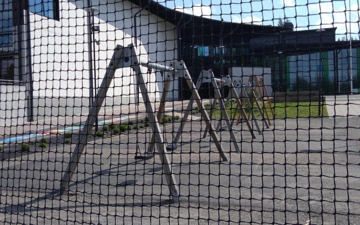 Tyhjiä keinuja verkon takana koulun pihalla
