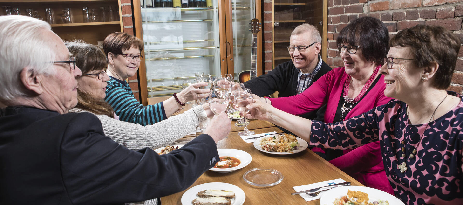 Kuvassa iloisia ikäihmisiä syömässä yhdessä saman pöydän ääressä.